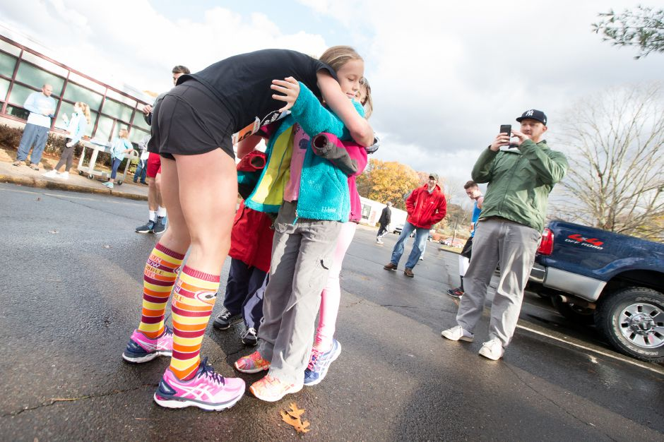 Anna Hladky of Wallingford gets a hug at the finishline from Evelyn 9, Maybeline 7 and Creason 4 with dad Jeff Sunday during the Kiwanis Club 5 mile and 5K Turkey Trot Road Race at Stevens Elementary School in Wallingford November 19, 2017 | Justin Weekes / For the Record-Journal