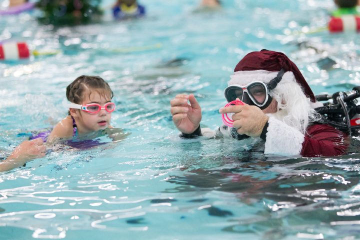 Capri Kobrin 5 of Wallingford swims to Stephen Domorod as Scuba Santa to get a ring ornament for the floating Christmas tree Sunday during the annual Scuba Santa at the Wallingford YMCA in Wallingford Dec. 11, 2016 | Justin Weekes / For the Record-Journal