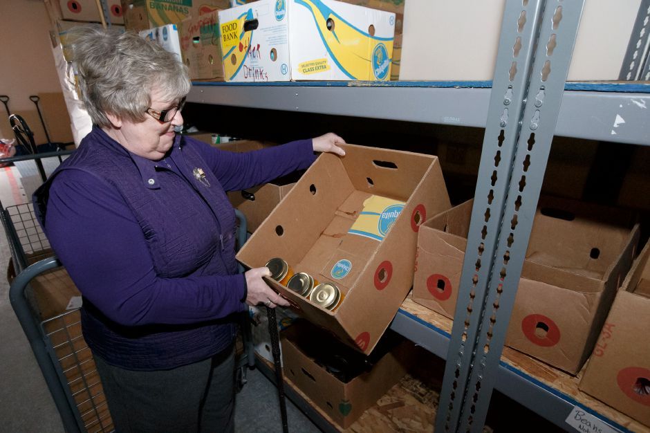 Gail Powell, board chairwoman, pulls out an almost empty box of canned goods Monday at Masters Manna in Wallingford February 19, 2018 | Justin Weekes / Special to the Record-Journal