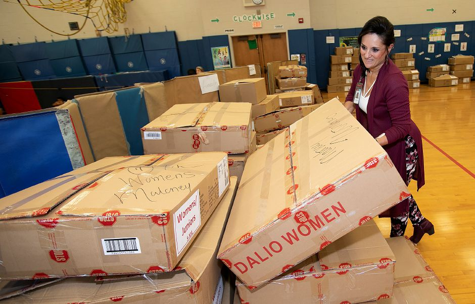 Shirley Couturier, district volunteer coordinator for the Meriden Board of Education, sets down a box of coats during the annual coat donation by the Dalio Foundation at Hanover School in Meriden, Thursday, Oct.11, 2018. Over one thousand children in Meriden's public school system received new coats on Thursday to prepare for the winter months. Dave Zajac, Record-Journal