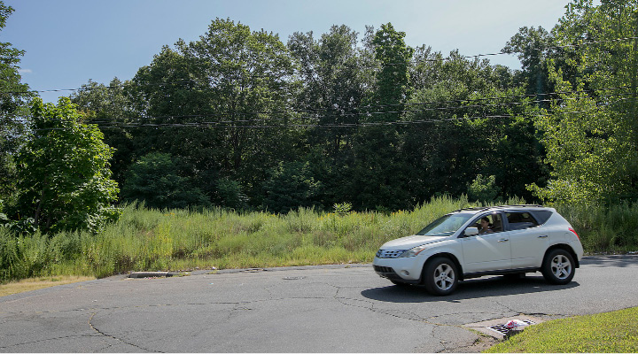 A motorist passes a vacant lot on Edgewood Street off the Chamberlain Highway in Meriden, Friday, August 25, 2017. A development group is requesting a zone change to allow a senior apartment building to be constructed at the location.   | Dave Zajac, Record-Journal