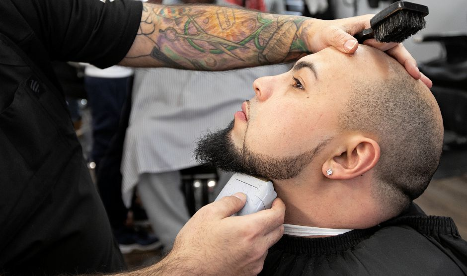 Barber David Ortiz, owner of Classic Cutz, shaves the beard of longtime customer, Larry Velez, of Hamden, at the new shop at 35 N. Colony Rd. in Wallingford, Fri. Feb. 8, 2019. Dave Zajac, Record-Journal