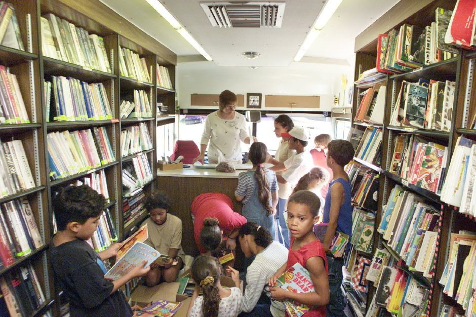 Librarian Alexis Burgess, center, assists children from the Chamberlain Heights housing project with their book selections Tues., Aug. 15 in the Meriden Public Library