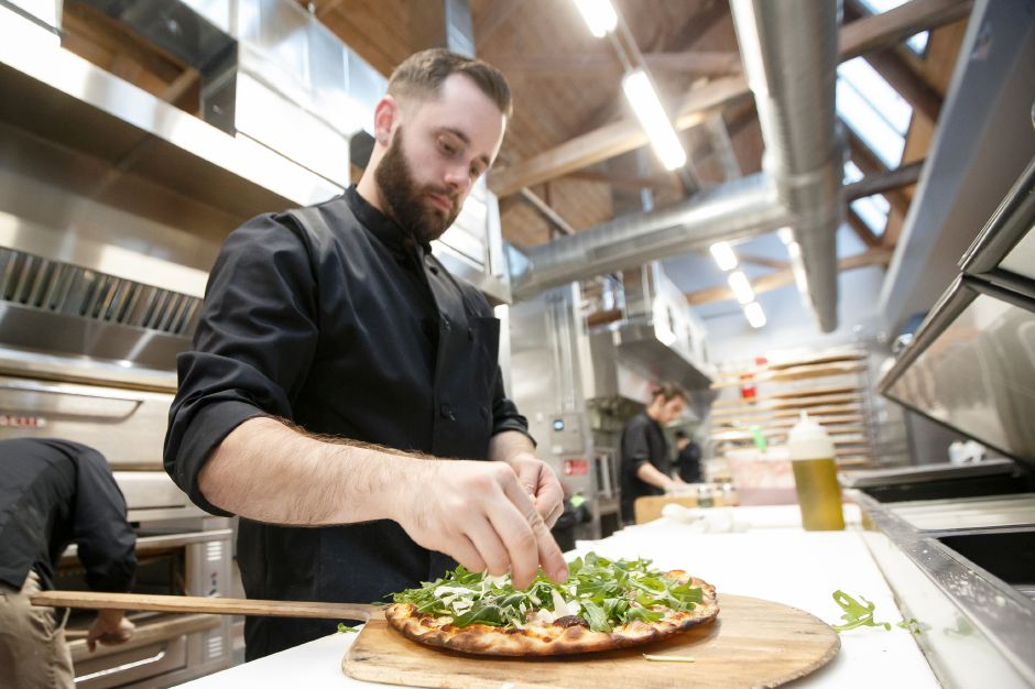 Chris Jolly builds a specialty pizza Saturday at Sauced at Kinsmen in the Kinsmen Brewery in Southington February 10, 2018 | Justin Weekes / Special to the Record-Journal