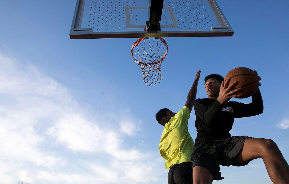 Kamron Moreno, 16, of Meriden, leaps for a shot as Quanell Grimes, 16, of Meriden, defends during a game of basketball Tuesday at Habershon Park in South Meriden.Dave Zajac, Record-Journal
