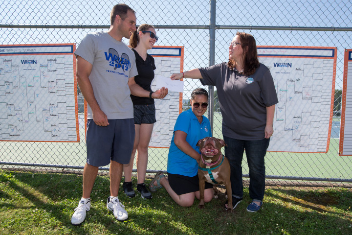 "Matt and Joanna Wayton, left, present a $2,000 check Sunday to Wayton Open tournament benefactors Danielle Boccher (kneeling) and Debbie Maas of Thank Dog Rescue. Boccher and Maas are with ""Sophie,"" a 4-year old pit bull mix. 