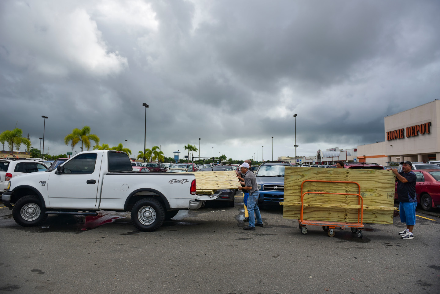 Men load recently purchased wood panels to be used for boarding up windows in preparation for Hurricane Irma, in Carolina, Puerto Rico, Tuesday, Sept. 5, 2017. Irma grew into a dangerous Category 5 storm, the most powerful seen in the Atlantic in over a decade, and roared toward islands in the northeast Caribbean Tuesday. (AP Photo/Carlos Giusti)