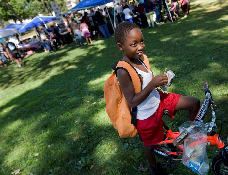 Nazai Wright, 7, of Meriden, sports a new backpack while sitting on his bike at the annual Back To School Expo at City Park in Meriden, Tuesday, August 23, 2016. | Dave Zajac, Record-Journal