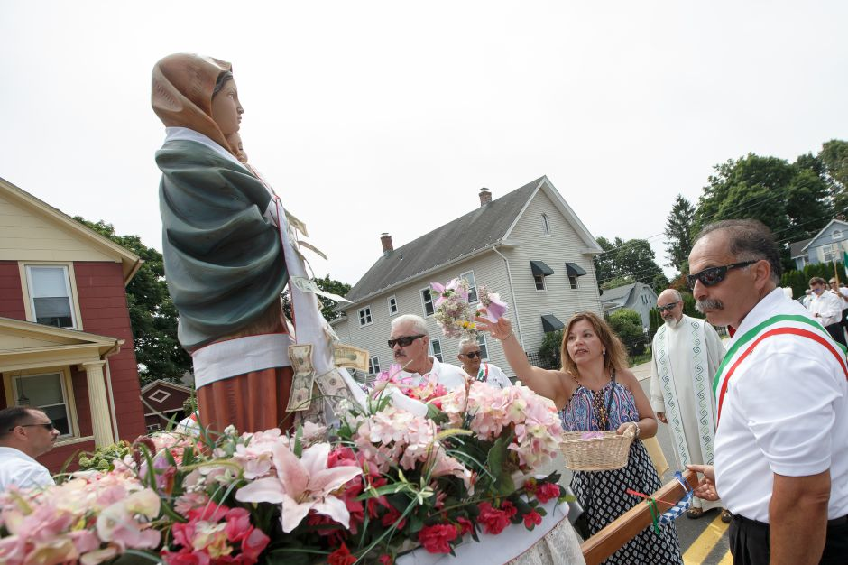Maria Della Porta of Southington adorns the Madonna Della Strada Sunday during an outdoor mass in celebration of the Italian Festival in Southington July 29, 2018 | Justin Weekes / Special to the Record-Journal