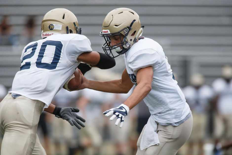 Platt quarterback Lorenzo Sanson hands off to sophomore running back Roberto Salas during Friday's preseason scrimmage with Simsbury at Falcon Field. Salas, looking to step in for injured senior E.J. Dudley, got loose for a 60-yard touchdown run. | Justin Weekes / Special to the Record-Journal