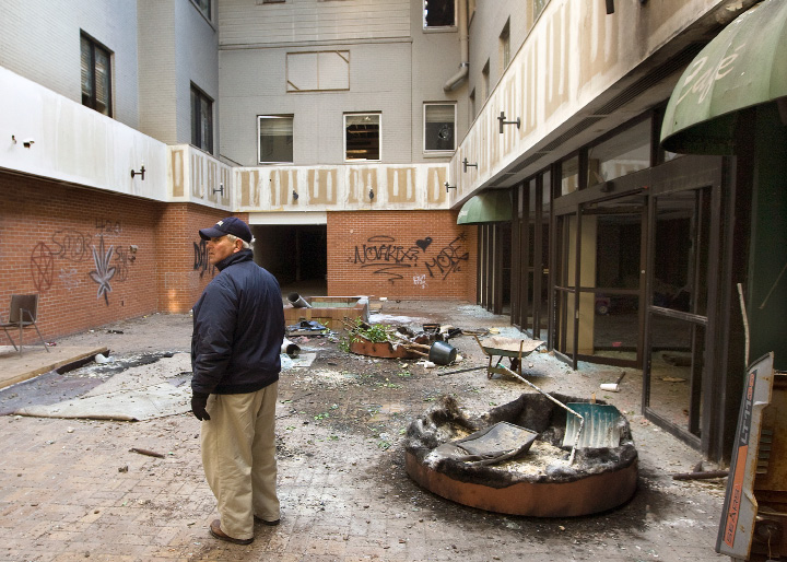 Dominick Caruso, city planner, looks over the main entrance to the former Meriden-Wallingford hospital while touring the dilapidated building on Cook Avenue with city officials, police and fire personnel, Thursday, January 9, 2014.  |  Dave Zajac / Record-Journal