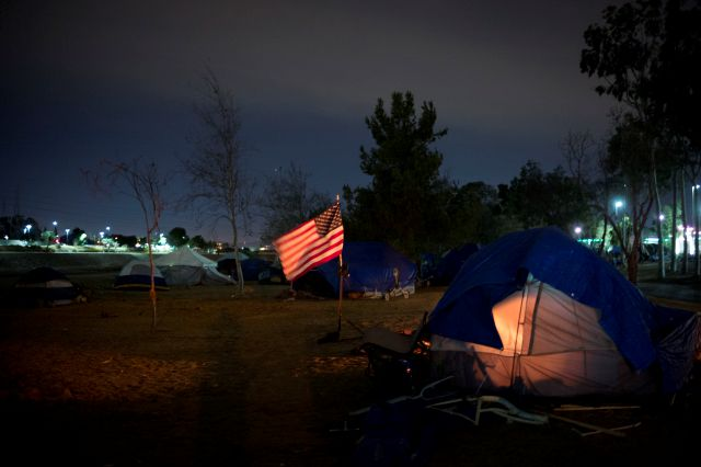 Homeless tents are pitched around an America flag along the Santa Ana River trail Sunday, Dec. 10, 2017, in Anaheim, Calif. Advocates say the homeless population has become more visible as police have cracked down on rules barring camping, driving people from parks and bus benches to a few centralized locations, such as the flood control channel along the Santa Ana River in Anaheim. (AP Photo/Jae C. Hong)
