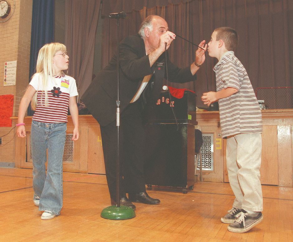 "RJ file photo - Charles ""Chick"" Kelman has second-grader Kevin Ferrone blow on a rope to make a knot disappear as Heather Daly, also a second-grader, watches, May 31, 1998 during a performance at Stevens School in Wallingford."