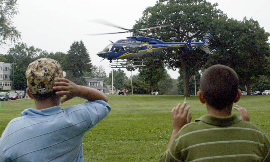 MERIDEN, Connecticut - Tuesday, August 7, 2007 - From left, Jonathan Pacheco 10, reaches up to keep his hat from blowing away, and his brother Brayan (cq) 8, blocks the strong wind from the take-off of the Connecticut State Police helicopter at Meriden