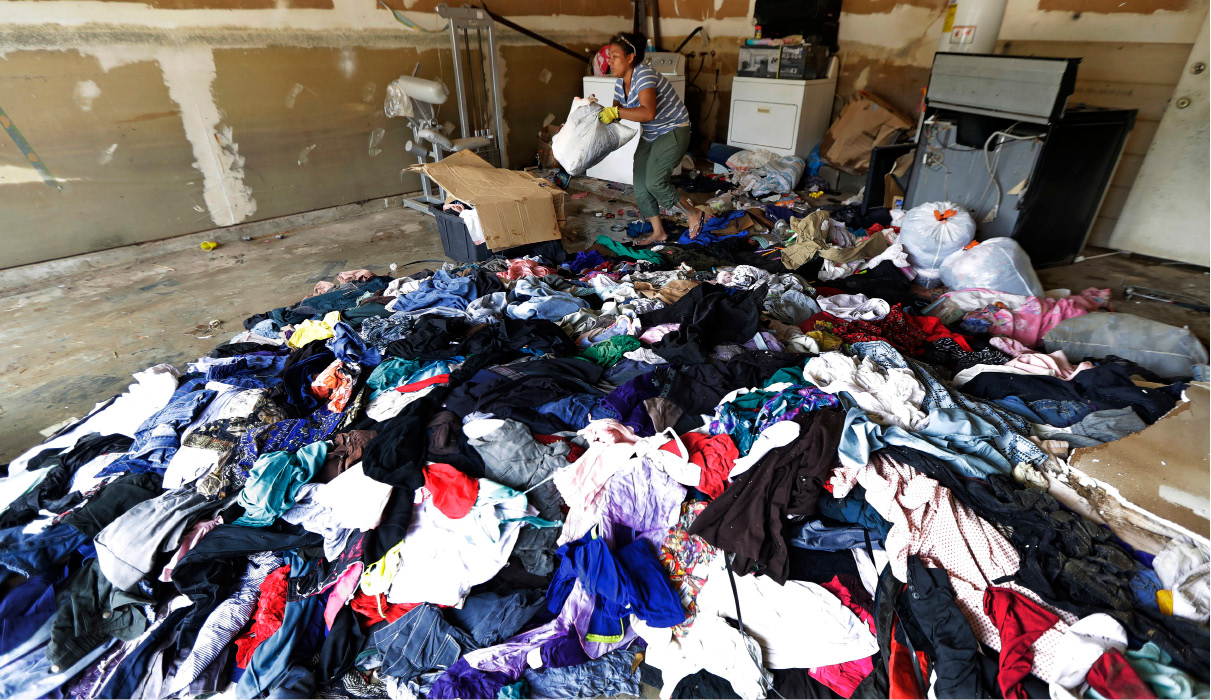 Julia Lluvia removes damaged clothing from her home which was severely damaged by floodwaters in the aftermath of Hurricane Harvey Monday, Sept. 4, 2017, in Houston. (AP Photo/David J. Phillip)