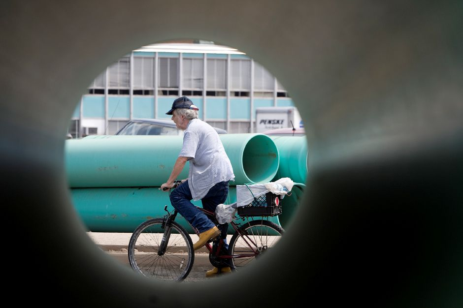 A bicyclist (seen through piping) rides along Gravel Street in front of Maloney High School where work on a drainage upgrade is ongoing Monday, August 17. 2015. | Dave Zajac / Record-Journal