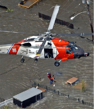 A resident is rescued from the roof top of a home by the U.S. Coast Guard as floodwaters from  Hurricane Katrina cover the streetsTuesday, Aug. 30, 2005 in New Orleans. (AP Photo/David J. Phillip)