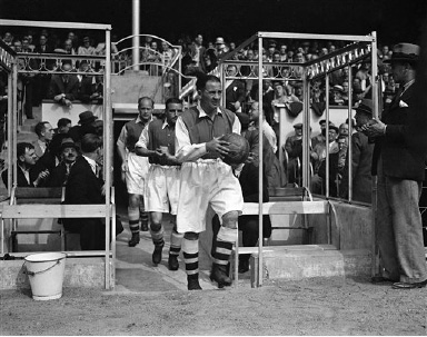 Arsenal captain Alex James leads out his team, for the first match of the season against Everton, at Highbury Stadium, London, on Aug. 29, 1936. (AP Photo)