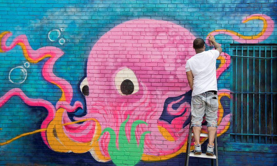 Artist Eddie Rivera, of Meriden, spray paints the tentacles of an octopus mural in the back of the Castle Craig Players building on West Main Street in Meriden, Thursday, July 13, 2017. | Dave Zajac, Record-Journal