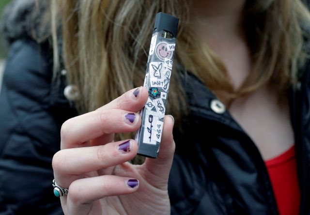 In this Wednesday, April 11, 2018 photo, an unidentified 15-year-old high school student displays a vaping device near the school