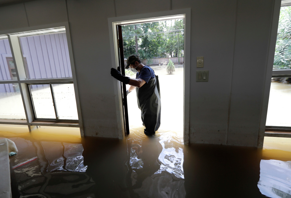 Juan Minutella opens the back door while helping friend Gaston Kirby collect the last of his belongings from his flooded home in the aftermath of Hurricane Harvey, Monday, Sept. 4, 2017, near the Addicks and Barker Reservoirs, in Houston. (AP Photo/David J. Phillip)
