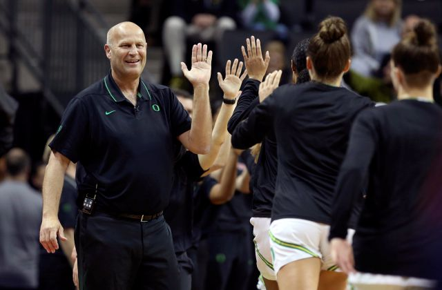 Oregon head women basketball coach Kelly Graves high fives his team before a women