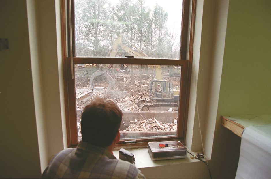RJ file photo - Gary Tablot, of Mercantile Construction, in South Boston, watches as an excavator rips apart a house on Broad Street in Meriden to make way for the new Stop & Shop, Dec. 22, 1998.