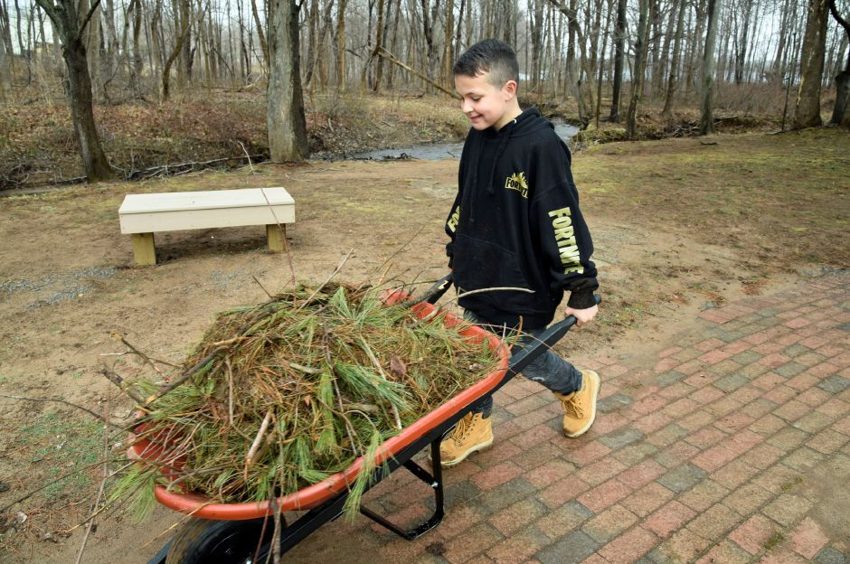 John McCarter, 8, carries twigs and weeds in a wheelbarrow at Allyn Brook Park, 50 Pickett Ln., on Saturday, April 6, 2019. | Bailey Wright, Record-Journal