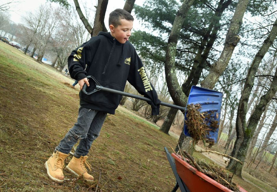 John McCarter, 8, rakes up twigs and weeds in Allyn Brook Park, 50 Pickett Lane, on Saturday, April 6. | Bailey Wright, Town Times