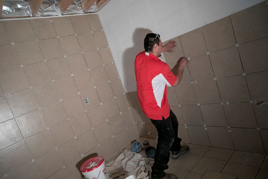 Jose DePaz, working for West Haven based Walter Hurley Tile and Marble, installs tile in a restroom as interior construction continues on Huxley