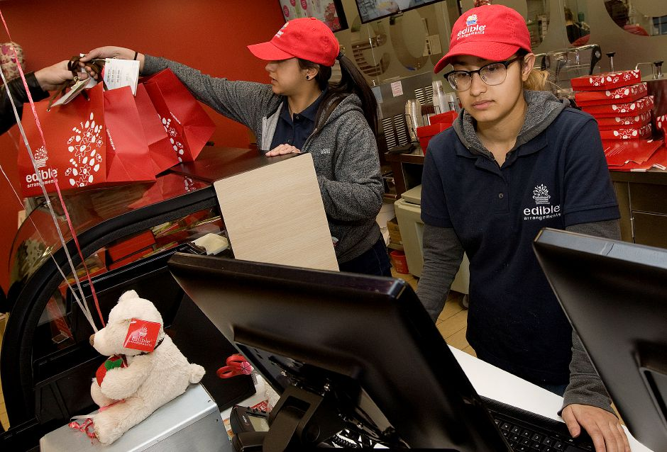 Customer service rep. Annmarie Castro, of Meriden, right, and Breanna Rivera, of Bristol, crewmember, left, help customers with orders at Edible Arrangements in Wallingford, Monday, February 13, 2017. | Dave Zajac, Record-Journal