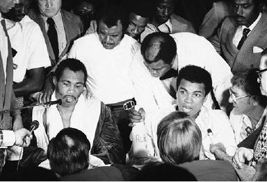 Muhammad Ali, right, expounds on his victory over Ken Norton in a post-fight interview at the Forum in Inglewood, California on Monday, Sept. 10, 1973 after gaining a split decision in their 12-round re-match. Glum-looking Norton listens at left. (AP Photo)