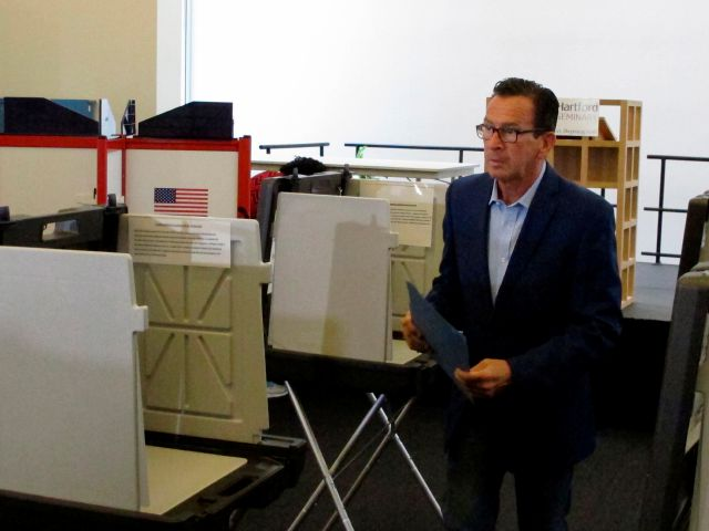 Gov. Dannel P. Malloy prepares to submit his ballot for the primary election at a polling place in Hartford, Conn., on Tuesday, Aug. 14, 2018. The Democratic governor is not seeking a third term. The Connecticut primary elections feature candidates for governor, lieutenant governor, Congress and other statewide offices. (AP Photo/Dave Collins)