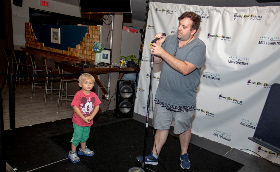 Patrick Laffin, right, gets a microphone ready for open mic night on Wednesday at the Square Foot Lounge next to four-year-old  son Jamie.