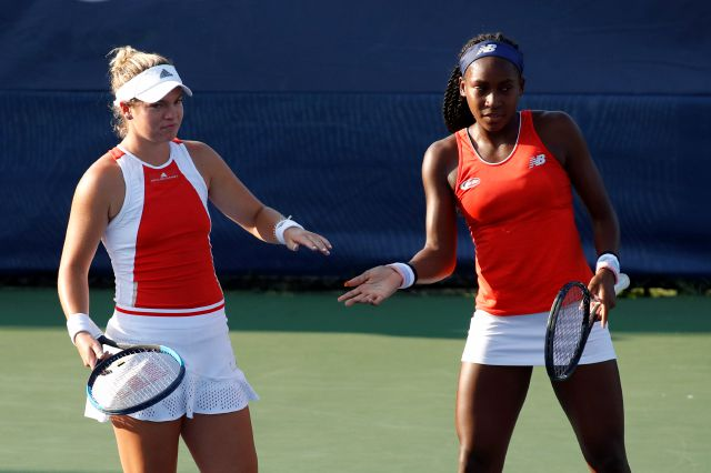 Caty McNally, left, slaps hands with Cori Gauff as they play the women