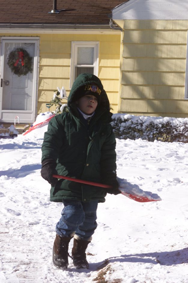 Austin Walls, 5, of Meriden shovels the homemade snow from his family