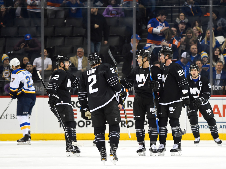 New York Islanders left wing Anders Lee (27) celebrates his goal with teammates as St. Louis Blues defenseman Alex Pietrangelo (27) skates away in the first period of an NHL hockey game in New York, Thursday, Dec. 8, 2016. (AP Photo/Kathy Kmonicek)