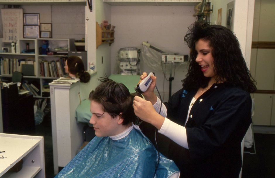 RJ file photo - Wilcox Tech junior Lisa Benney administers a custom haircut to freshman Donald Stewart, Feb. 1994. Haircut rates at Wilcox are set by the state at one-half of retail.