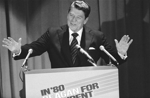 Former California Gov. Ronald Reagan raises his hands as he acknowledges applause at $500-a-plate GOP fundraising dinner in New York City on Tuesday, Nov. 14, 1979. Reagan used the dinner to formally declare his candidacy for the GOP presidential nomination. He spoke as simultaneously a taped version of his speech announcing his candidacy was being telecast nationally. (AP Photo/WJZ)