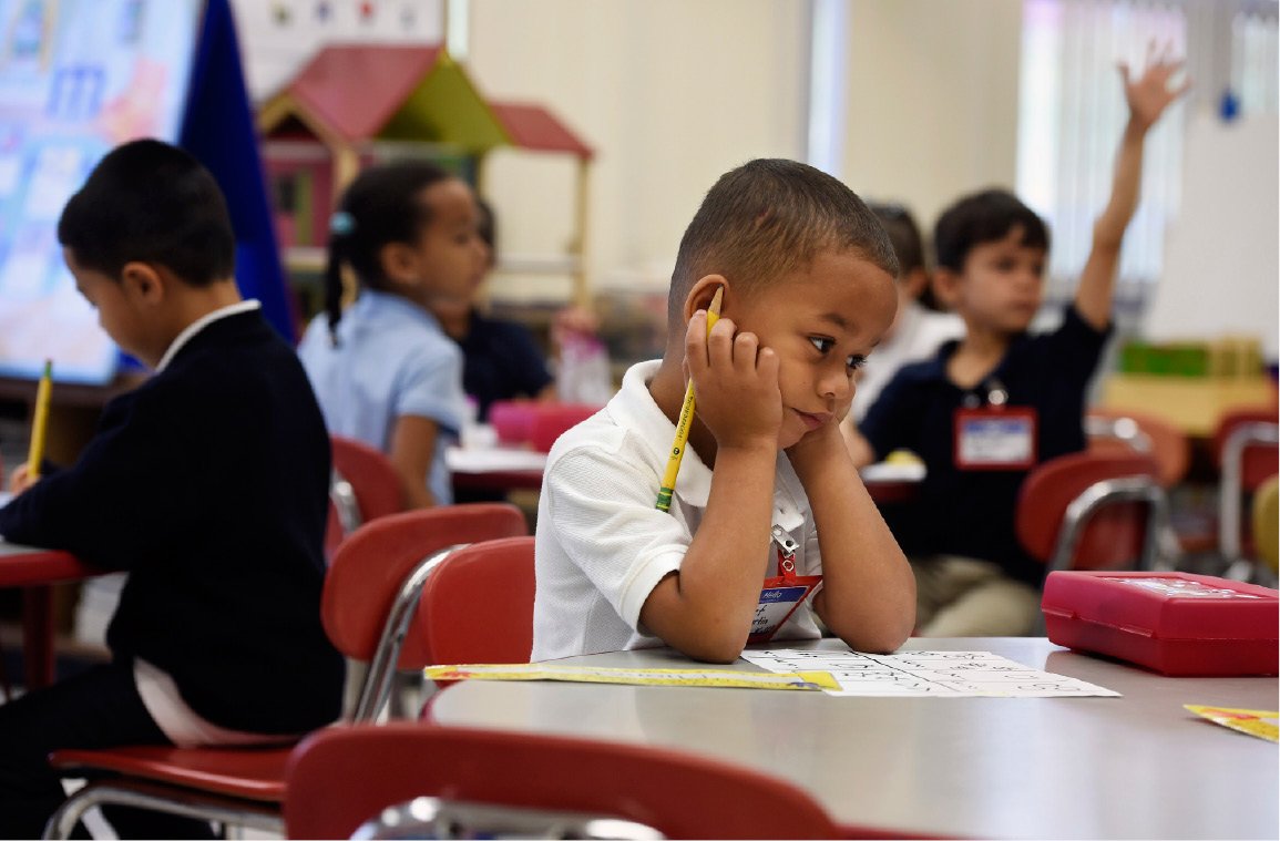 In this Friday, Sept. 29, 2017 photo, Elionet Saez Martin, of Puerto Rico, works at his desk in his kindergarten class at Chamberlain Elementary School in New Britain, Conn. As Hurricane Maria churned toward Puerto Rico, his mother put him and his 9-year-old brother, Eliot, on a plane to be with their grandfather in Connecticut. The brothers are among the first of what is expected to be large numbers of Puerto Rican children enrolling in school districts on the U.S. mainland, particularly in urban areas from Florida to Massachusetts with large Puerto Rican populations.  (AP Photo/Jessica Hill)