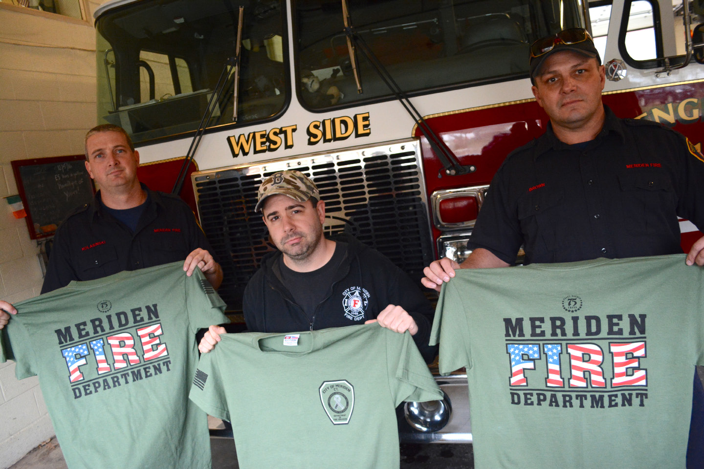 Meriden firefighters Eric Kolasinski, Kris Leahy and Ken Brown hold up Meriden Fire Department Pearl Harbor T-shirts at Station 1 on Tuesday.| Bryan Lipiner, Record-Journal
