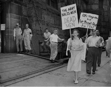 Demonstrators carrying signs protest draft registration in front of the Cadet Armory in Boston, Mass., Aug. 30, 1948. (AP Photo)
