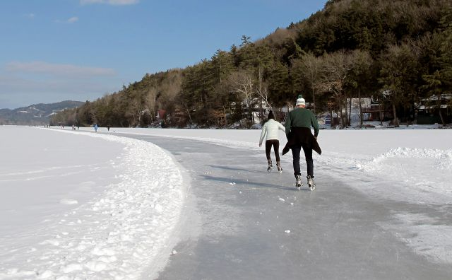 In this Jan. 20, 2018 photo, ice skaters travel along a 4.5-trail around Lake Morey in Fairlee, Vt., said to be the longest Nordic skating trail in the United States. (AP Photo/Lisa Rathke)