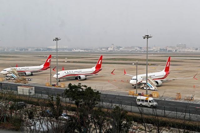 In this photo taken Monday, March 11, 2019, three Shanghai Airlines Boeing 737 Max 8 passenger planes are parked at the Hongqiao Airport in Shanghai, China. U.S. Aviation experts on Tuesday, March 12, 2019 joined the investigation into the crash of an Ethiopian Airlines jetliner that killed 157 people, as a growing number of airlines grounded the new Boeing plane involved in the crash. (Chinatopix via AP)