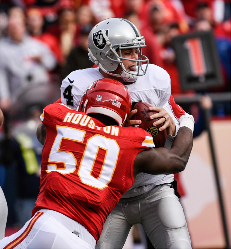 FILE - In this Dec. 14, 2014, file photo, Kansas City Chiefs outside linebacker Justin Houston (50) sacks Oakland Raiders quarterback Derek Carr (4) during the first half of their NFL football game,  in Kansas City, Mo. The Raiders are 10-2 and leading the AFC West, one of the surprise teams in the NFL, while the Chiefs are 9-3 with a win over Oakland already in their pocket. The winner of their primetime matchup at frosty Arrowhead Stadium on Thursday, Dec. 8, 2016, will have the inside track on ending a lengthy division title drought, not to mention the potential for a first-round playoff bye and a home game in the second round. (AP Photo/Reed Hoffmann, File)