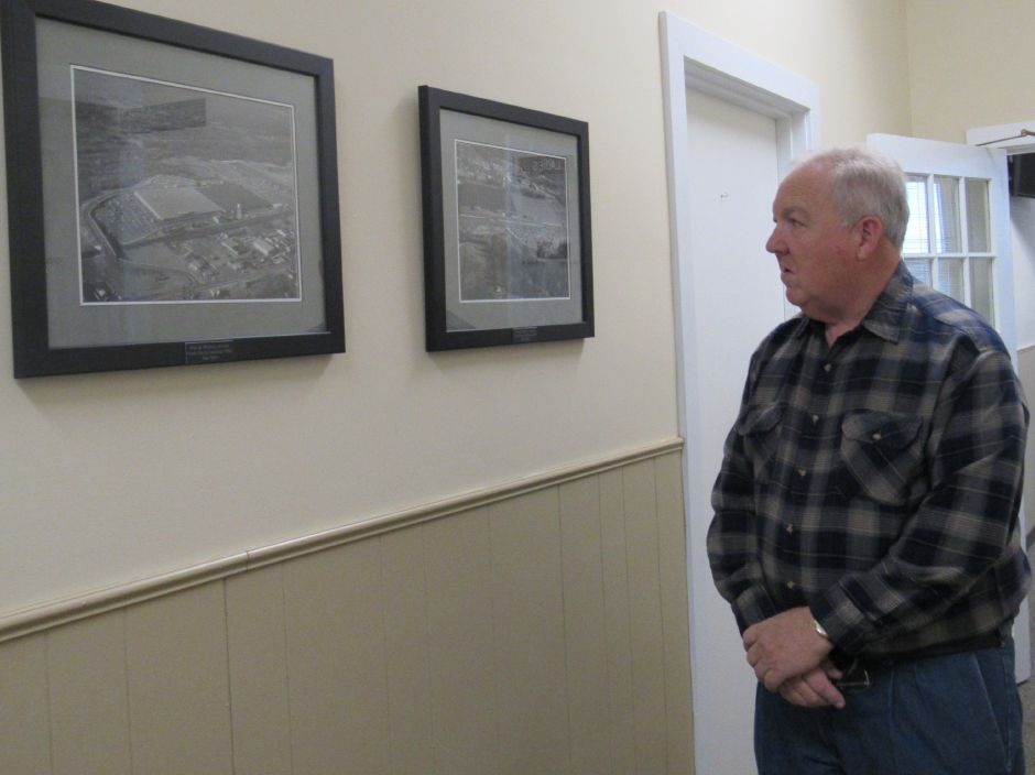 Former Pratt & Whitney employee Bill Richards views framed prints of historic photos of the plant site he donated to the town  on Wednesday, Dec. 6, 2017. | Lauren Takores, Record-Journal