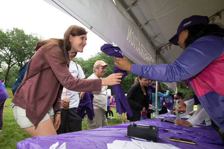 Kathlyn Oliberio of East Haven pick her shirt up at registration Saturday during the PurpleStride 5k and walk fundraiser for Pancreatic Cancer Action Network at Hubbard Park in Meriden Jun. 17, 2017 | Justin Weekes / For the Record-Journal