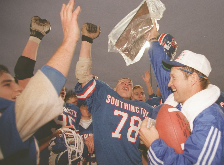 RJ file photo - A jubilant coach Jude Kelly holds up the Class LL championship plaque to the cheers of Southington players, including lineman Mike Carbone, Dec. 5, 1998.