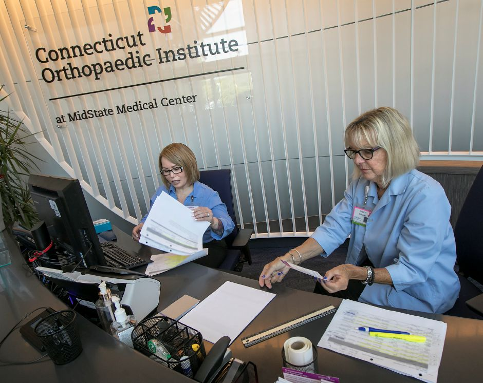 Marisol Carrero, financial counselor, left, and Cheryl Solecki, volunteer, work at the front desk of the Connecticut Orthopaedic Institute at MidState Medical Center in Meriden.