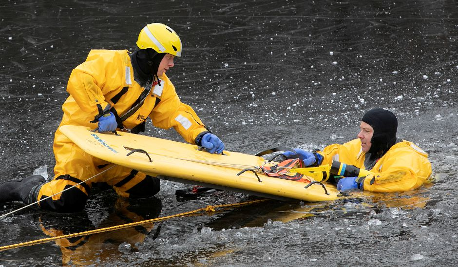 Southington firefighters Luke Martin, left, and Derek Dion, right, practice a cold water rescue at a pond off Mandel Drive in Southington, Wed., Jan. 16, 2019. Dave Zajac, Record-Journal